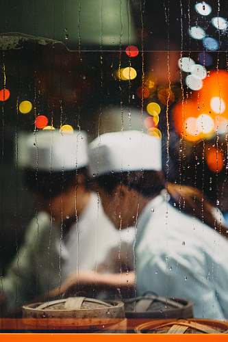 human two persons in white hats taken from glass frame with waterdrops people