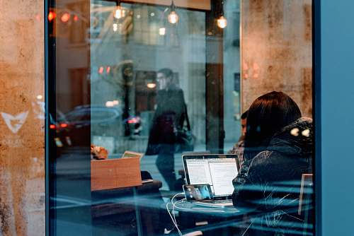 human woman inside a building using her laptop people