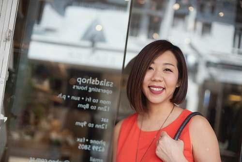 human woman leaning on glass wall panel happy teacher