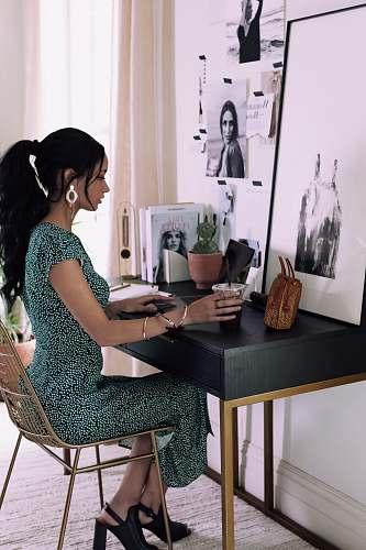 human woman sitting beside table inside room sitting