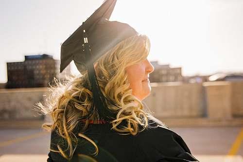 people woman wearing academic regalia during daytime woman