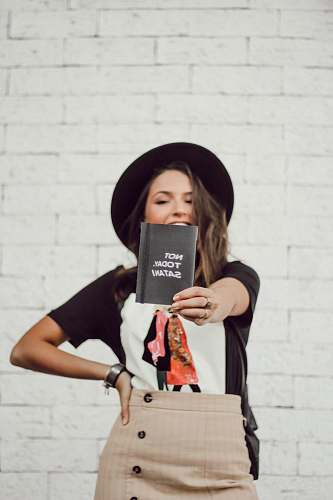 human woman with left arm akimbo standing and smiling while holding booklet apparel