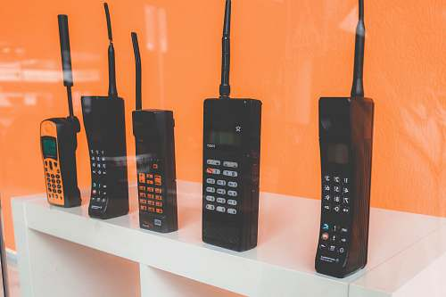 electronics five assorted-brand wireless phones on desk cell phone
