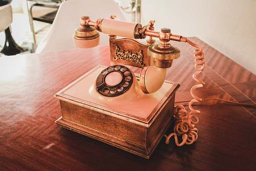 electronics white and brown rotary telephone on brown wooden table dial telephone