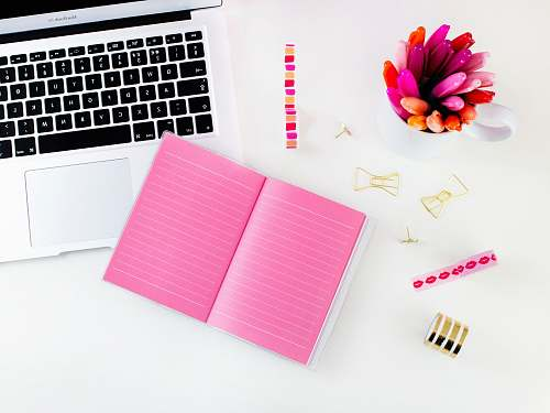 photo desk pink lined notebook beside MacBook Air blog free for commercial use images