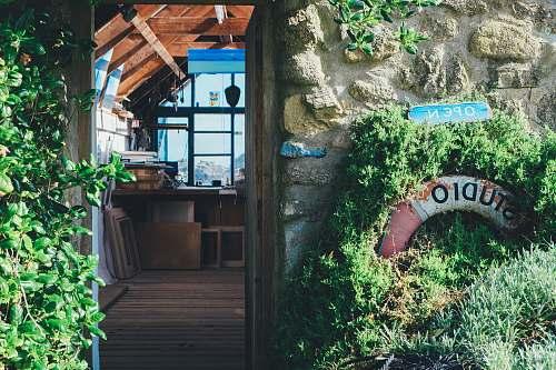 open brown wooden resthouse near garden flora