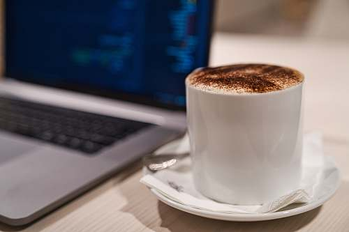 saucer cappuccino in cup on saucer beside laptop laptop