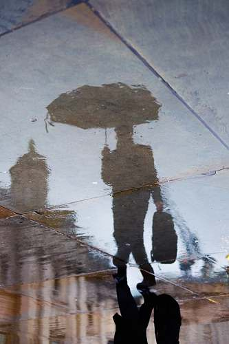 london reflection of person holding bag and umbrella smart