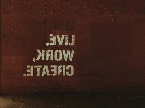 inspiration red brick wall with live, work, create. quote words