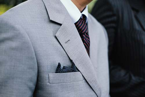 grey man wearing gray notched lapel suit jacket standing overcoat