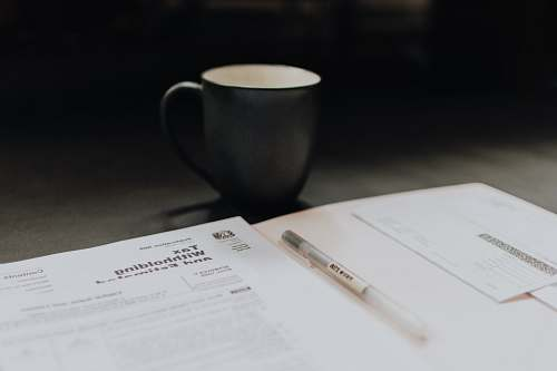 pen coffee mug near open folder with tax withholding paper diary