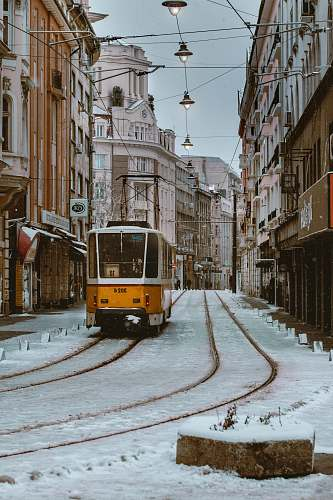 vehicle orange and gray train beside brown concrete building \ cable car