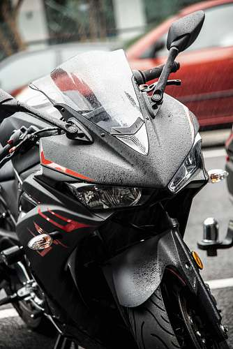 motorcycle black and red Yamaha R1 sports bike near parked car vehicle