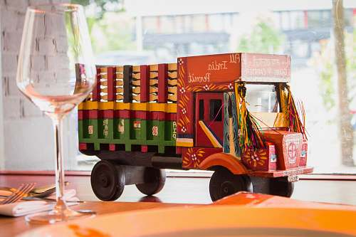 truck multicolored truck toy near wine glass vehicle