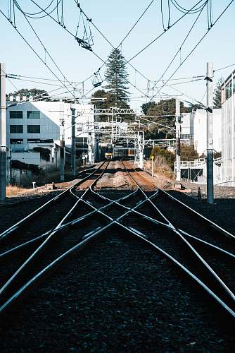 rail train tracks in the city during daytime railway