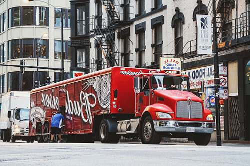 chicago man near red Budweiser trailer truck parked near concrete building during daytime vehicle