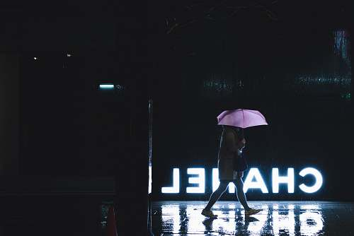 japan woman walking under umbrella passing by Chanel lighted signage canopy