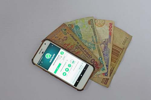 phone white Android smartphone beside banknotes fintech