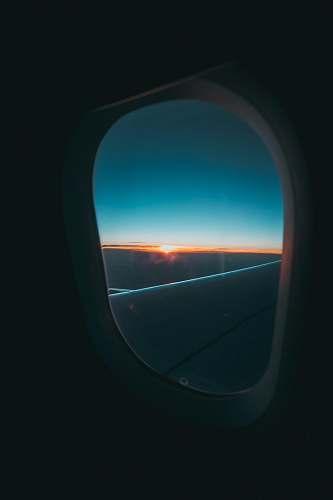 porthole window's plane photography of cloud mirror