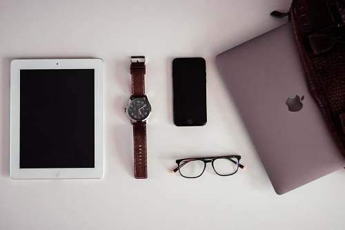 accessory white iPad beside round silver-colored analog watch, black iPhone 5 and black framed eyeglasses on white surface accessories