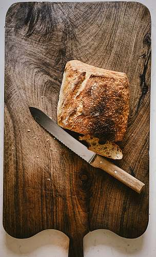 knife bread beside knife on chopping board weapon