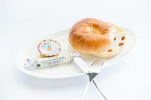 food bread on white plate with fork and table knife bagel