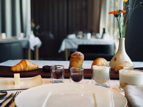 food four baked breads on brown wooden table beside shot glasses croissant