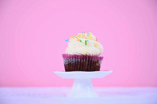 cream cupcake on white footed tray creme