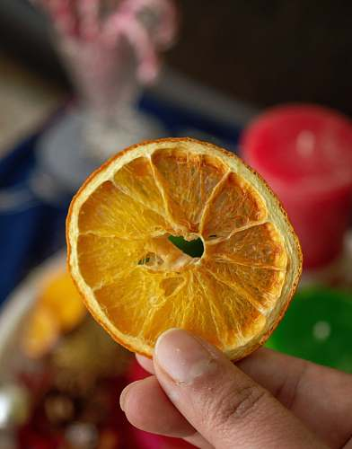 food selective focus photography of person holding sliced and dried fruit fruit