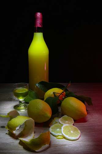 food sliced lemon beside glass bottle fruit