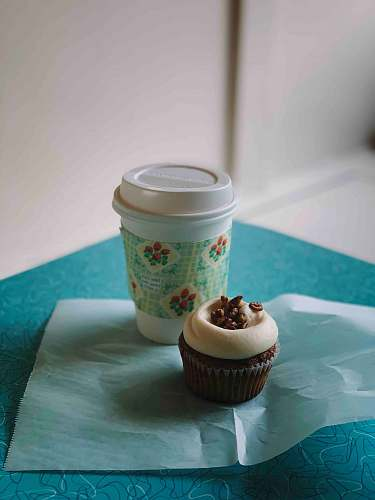 cake white and blue disposable cup beside chocolate cupcake cream