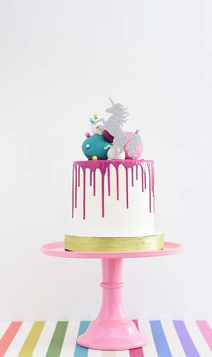food white and pink unicorn cake on a pink stand cake