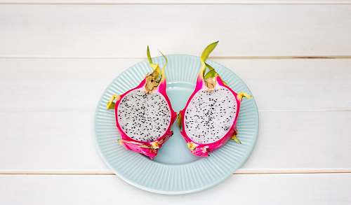 fruit 2-sliced dragon fruit in ceramic plate placed on wood plank dragon fruit