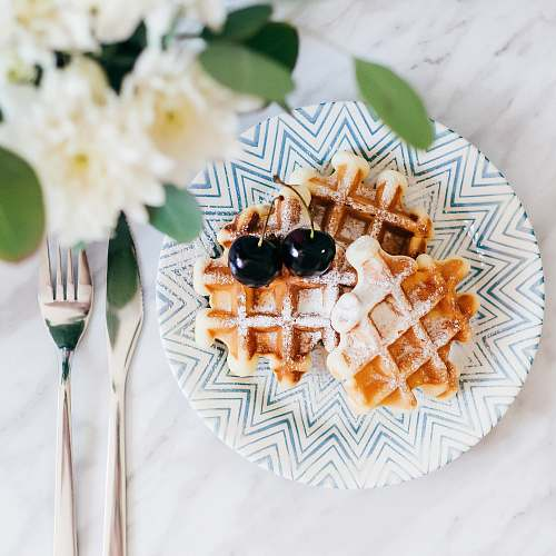 waffle 3 waffles on saucer with 2 cherry fruits beside fork and bread knife fresh