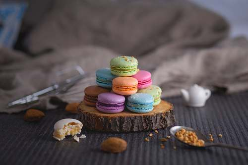 dessert assorted-color macaroons on wood slab cream