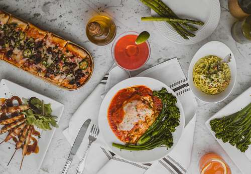 meal assorted dish on white ceramic plates pizza