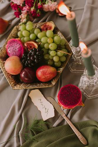 fruit assorted fruits in bowl near lighted green candles plant