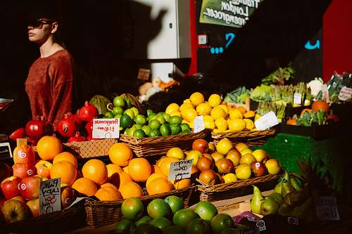 fruit assorted fruits on fruitstand beside woman in brown top citrus fruit
