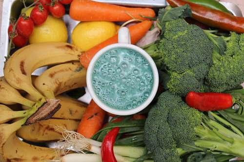 vegetable bananas, broccoli, and carrots beside white ceramic mug broccoli