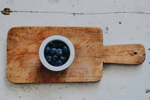 fruit blueberries on white saucer on chopping board blueberry
