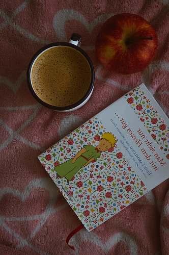 fruit book beside ceramic mug apple
