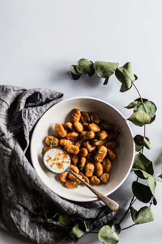 bowl bowl of nuts with spoon beside green leaves vegetable