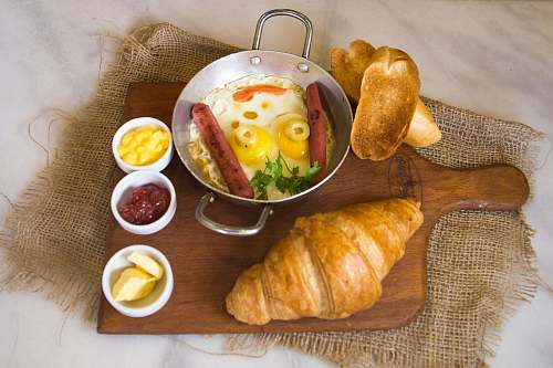 bread bread beside bowl with eggs and hotdog croissant