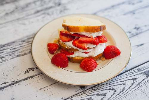 dessert bread with cream and strawberry slices on plate bread