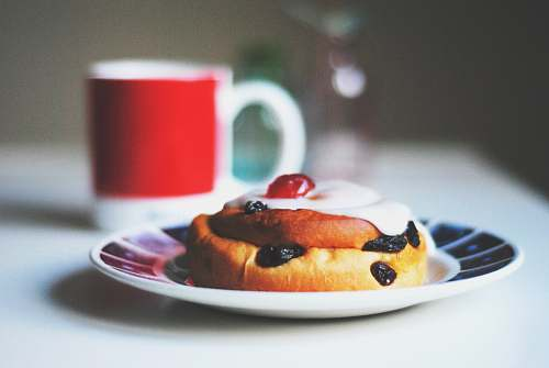 dessert bread with raisins on saucer beside white and red mug cup