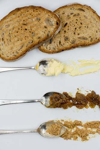 bread brown bread beside three spoons cutlery