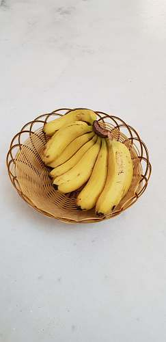 fruit bunch of yellow bananas in a brown wicker bowl banana