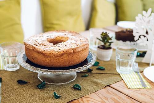 bread cake on stand beside cup bagel