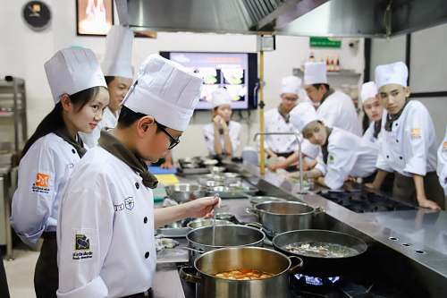 culinary chefs standing near cooking pots inside kitchen person