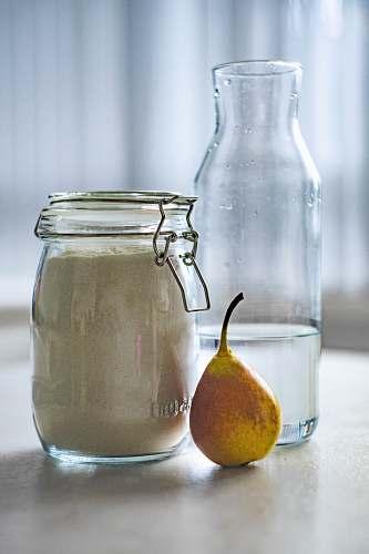 fruit clear glass jar near glass pitcher pear